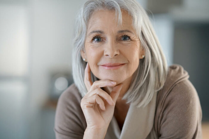 Senior woman looking at camera with hand on face