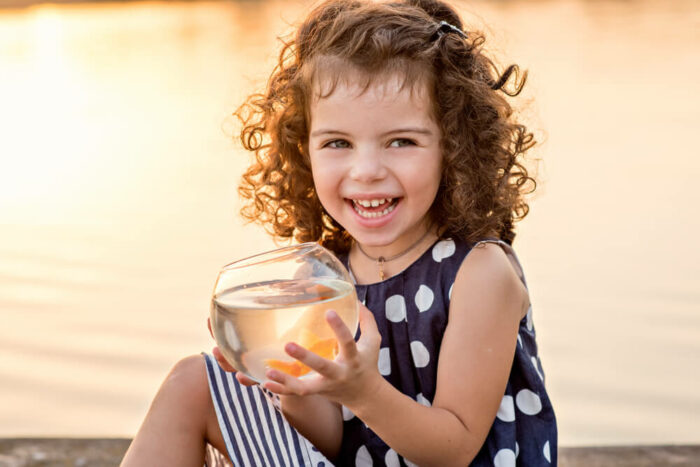 Little girl at lake with goldfish